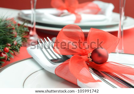Decorated christmas table setting in festive red white colours, napkin cutlery tied with organza ribbon and holiday bauble - stock photo