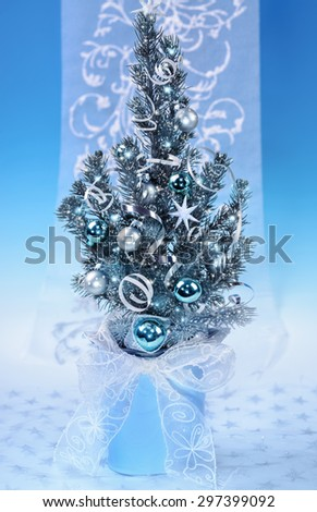 Decorated Christmas tree on blue winter background