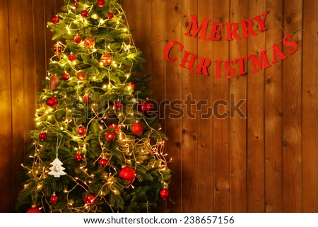 Decorated Christmas tree  on wooden wall background - stock photo