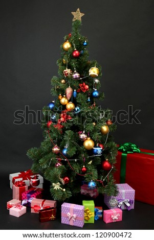Decorated Christmas tree with gifts isolated on black