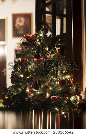 Decorated Christmas tree with lights on at home reflecting in smooth table