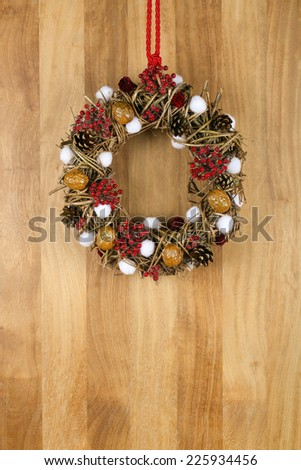 Decorated christmas wreath with red and white pillow hearts brown twigs walnuts and pine cones on sapele wood background, copy space - stock photo