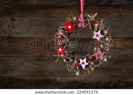 Decorated christmas wreath with red and white stars brown twigs gingham and polka dot on old wooden rustic background, copy space - stock photo