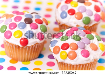 decorated cup cakes on spotty background - stock photo