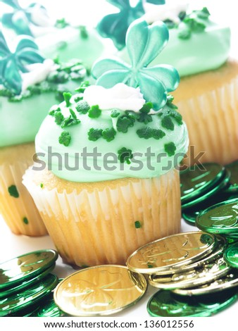 Decorated cupcakes in a festive St. Patrick's day setting with shamrocks. - stock photo