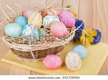 Decorated Easter eggs in and in front of a basket - stock photo