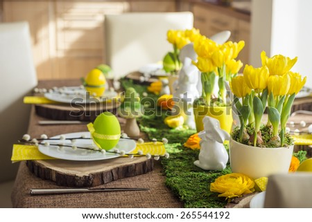 Decorated easter table with porcelain bunnies, eggs and flowers - stock photo
