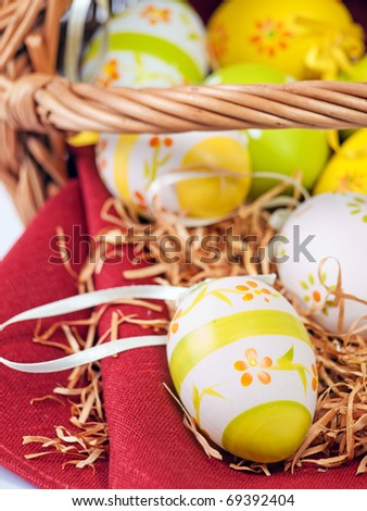 Decorated Easter wicker basket with colorful eggs on red wine napkin - stock photo