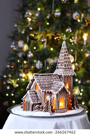 Decorated gingerbread church with Christmas tree on background - stock photo