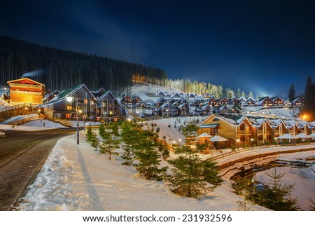 Decorated glowing home for Christmas Winter village, wooden houses in anticipation of the Christmas holiday. Lights and gerlyandy glow. From the pipe smokes. Around the forest and snow-covered slopes. - stock photo