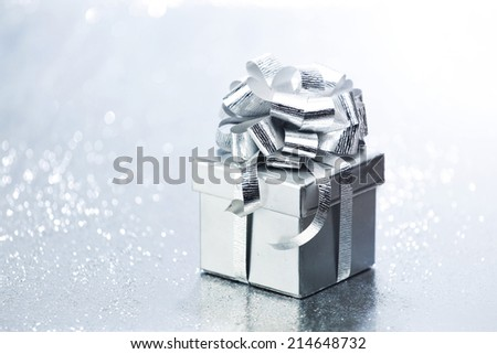 Decorated holiday gift on silver background - stock photo