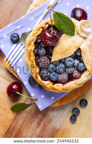 Decorated homemade shortcrust pastry berry pie with polka dot cloth, shiny metal icing sugar shaker, fork and selection of berries on grunge style wooden table. - stock photo