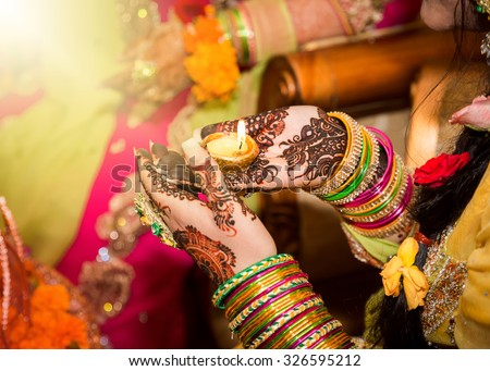 Decorated Indian bride holding candle in her hand. Focus on Hand. - stock photo
