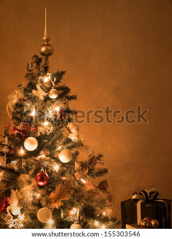 Decorated lit christmas tree with presents - stock photo