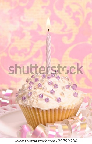 Decorated party cupcake with white lit candle and streamers - stock photo