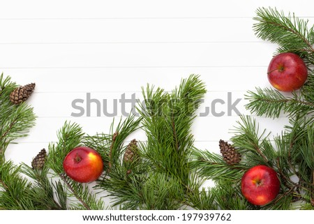 Decorated pine branches with cones and red apples on white wooden table,  free space - stock photo