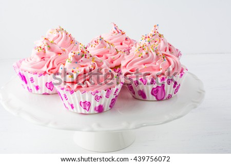 Decorated pink birthday cupcakes  on the cake stand. Sweet dessert  pastry with whipped cream. Birthday homemade cupcakes served for party. - stock photo