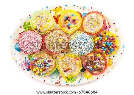 Decorated plate with colorful delicious cupcakes isolated over white - stock photo