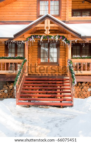Decorated porch of snowcapped Christmas wooden mansion - stock photo