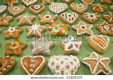 Decorated star and heart cookies on green paper - stock photo