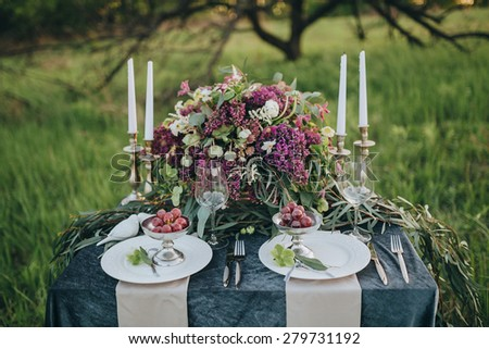 decorated table for two with a dark cloth decorated with floral composition of lilac and green candles on a background of grass and orchard - stock photo