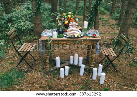 Decorated table for two with floral composition of white candles on a background of grass and woods - stock photo