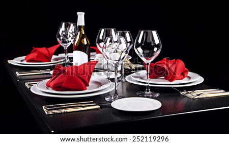 Decorated table in restaurant on black background - stock photo