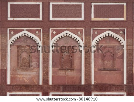 Decorated wall with three false windows under white arch at Agra Fort Palace in India. Fine stone carvings in red sandstones trimmed by white lines. - stock photo