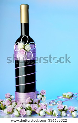 Decorated wedding bottle of champagne with roses, white pillow and two ring isolated  - stock photo