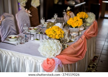 decorated wedding table, wedding preparation, serving, empty glasses and plates on the table, yellow flowers - stock photo