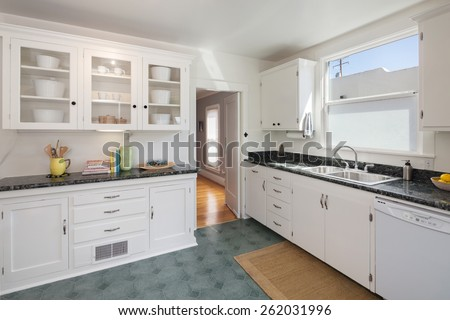 Decorated white kitchen with cabinet, vintage oven and black ornamented granite counter top. - stock photo
