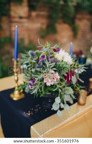 decorated with a festive table cloth, flower arrangement of flowers and greenery, candles and other decorations