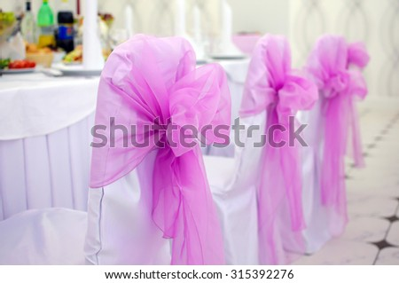 Decorated with bows chairs, pink. Banquet table setting. Serving dishes, Wedding evening. Wedding chair with bow. Pink big bow wedding decoration of the hall. Decor with white tablecloth.  - stock photo