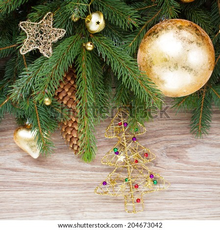 decorated with golden decorations green fir tree  on wooden background - stock photo