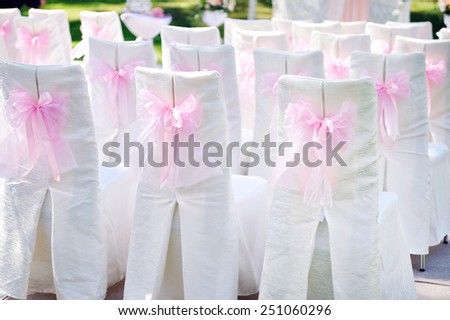 decorated with pink bows on the chairs wedding ceremony. - stock photo