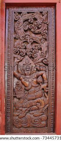 Decorated wooden beside door in Buddhist temple, Laos - stock photo