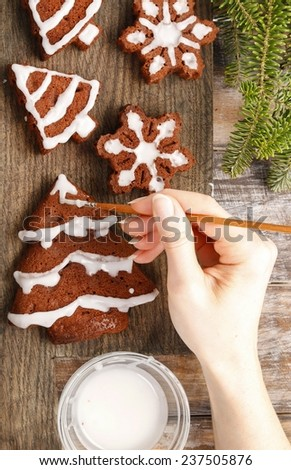 Decorating christmas gingerbread chocolate cookies with white icing - stock photo