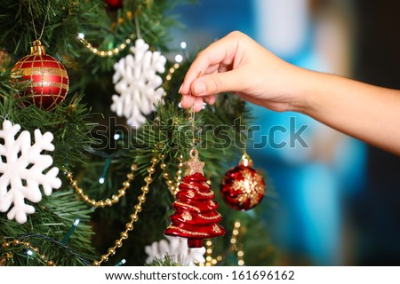Decorating Christmas tree on bright background - stock photo