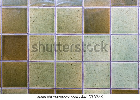 Decorating green ceramic wall and floor tiles with earth tones pallet. - stock photo