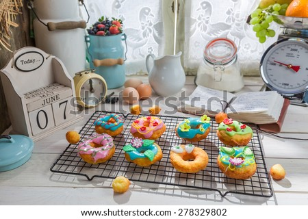 Decorating sweet donuts in the rustic kitchen