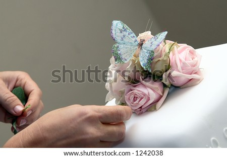 Decorating white wedding cake with roses and butterfly. - stock photo