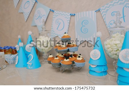 decoration for birthday holiday blue caps and cans of juice and a bowl with cookies - stock photo