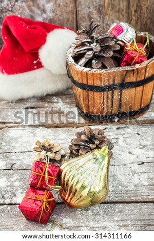 Decoration for the winter holidays.Decorative wooden tub filled with Christmas ornaments and pine cones - stock photo