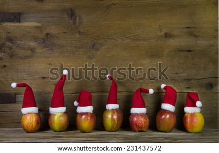 Decoration: Funny christmas greeting card with seven red santa hats on apples with wooden background. - stock photo