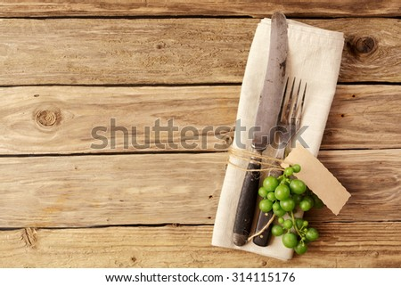 Decoration of a nAutumn like cutlery with a serviette on brown board with copyspace - stock photo