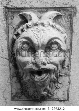 decoration of an ancient building in Italy of a demon in stone