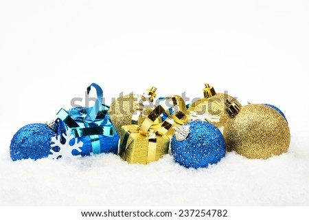 Decoration of blue and golden christmas baubles and gifts in line on snow white background - stock photo