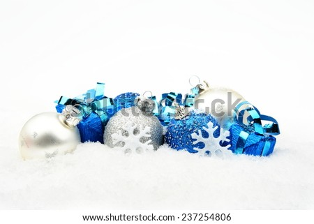 Decoration of blue,silver christmas baubles and gifts on snow white background - stock photo