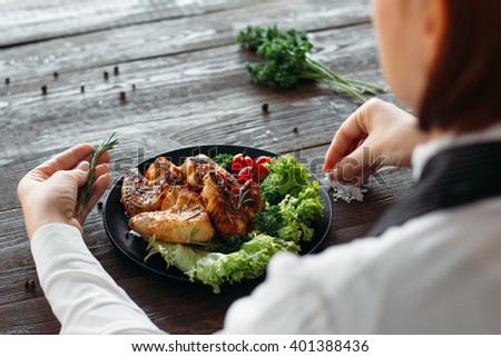 Decoration of chicken wings on wooden table. Chief prepares grilled spicy chicken with fresh vegetables. Over the shoulder view on food decoration.  - stock photo