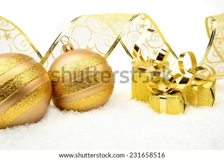 Decoration of golden christmas gifts,baubles,ribbon on snow withon white - stock photo